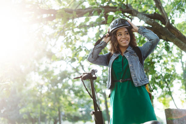 Happy young woman standing outside and putting on helmet stock photo
