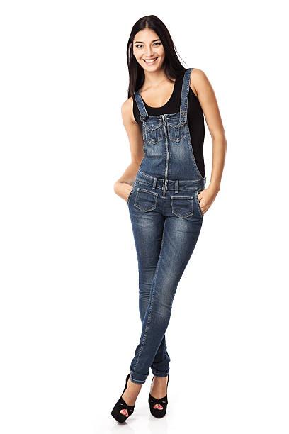 glückliche junge frau stehend mit händen in den taschen - jeans overall stock-fotos und bilder
