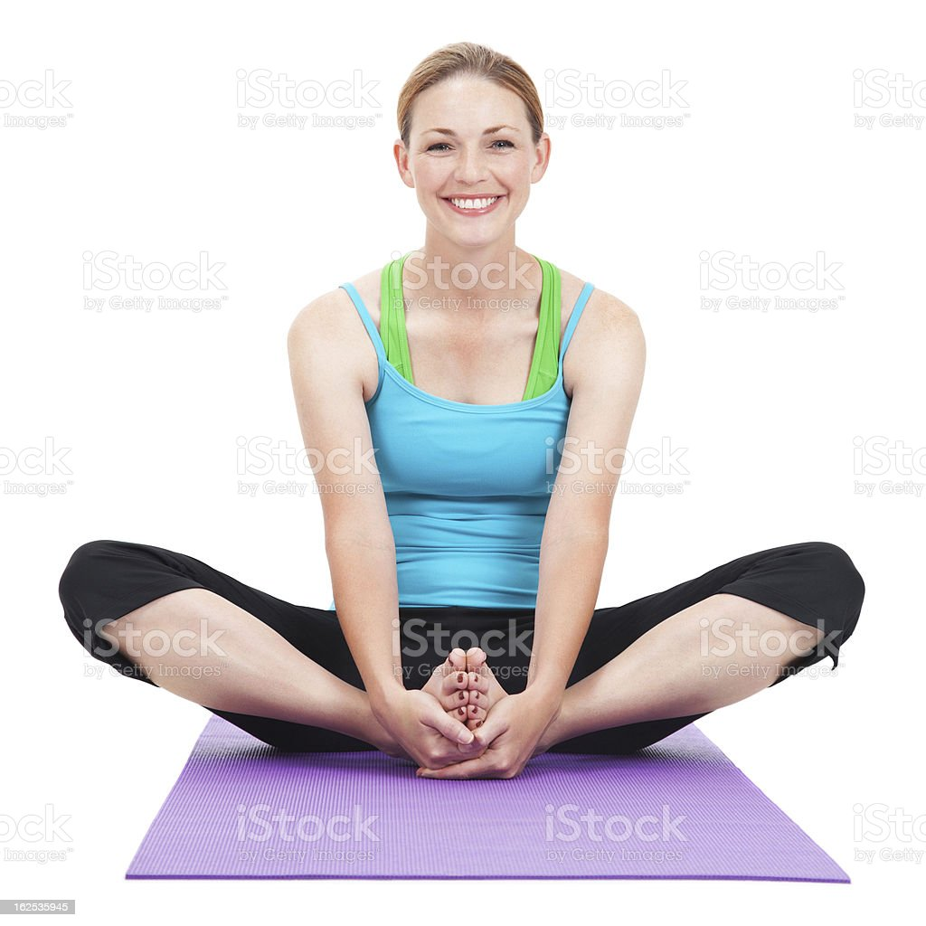 Happy Young Woman Stretching Legs on Yoga Mat royalty-free stock photo