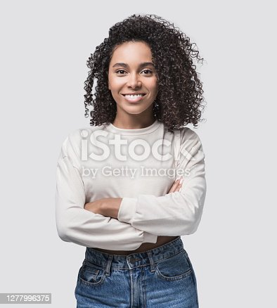Beautiful student girl with crossed arms looking at camera. Studio shot. Isolated on gray background