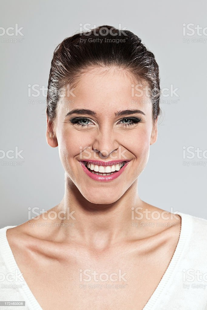 Happy young woman, Studio Portrait Portrait of excited young woman smiling at the camera. Studio shot on a grey background. 20-24 Years Stock Photo