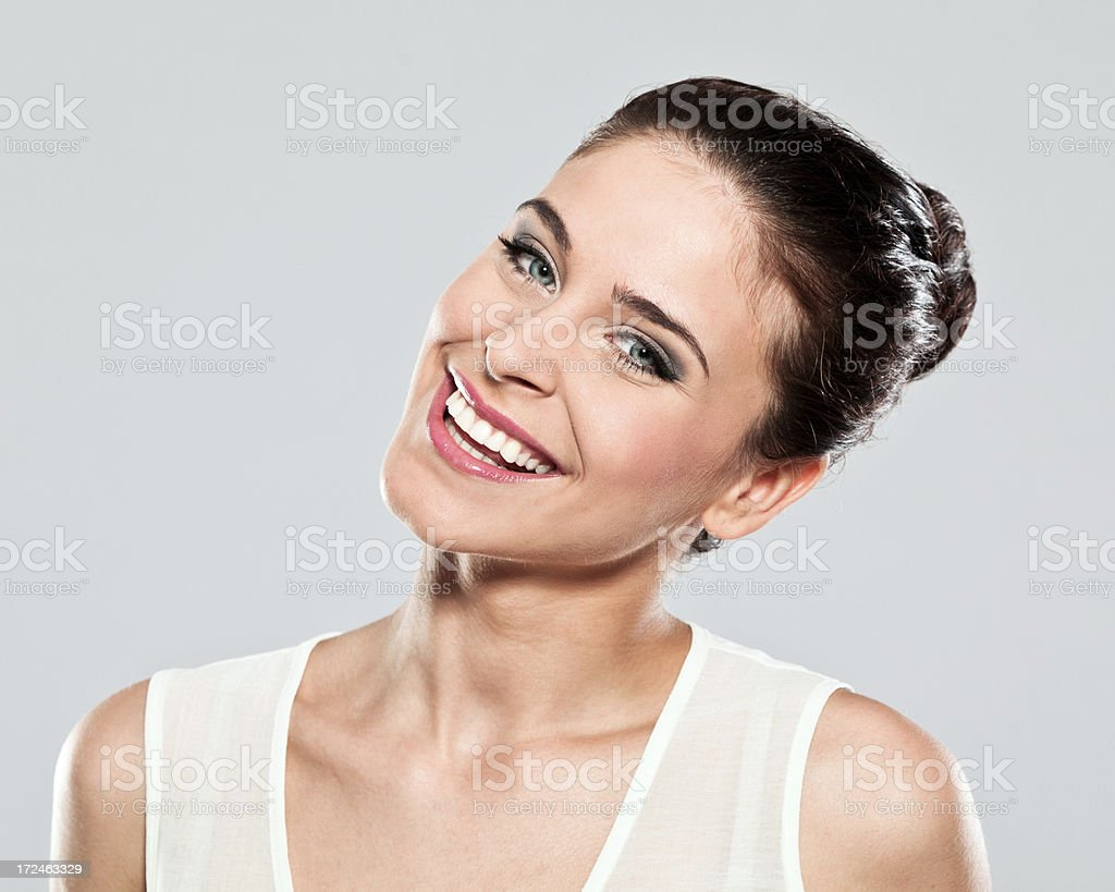 Happy young woman, Studio Portrait Portrait of happy young woman smiling at the camera. Studio shot on a grey background. 20-24 Years Stock Photo