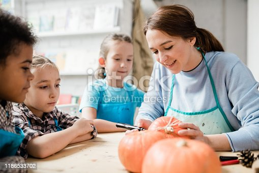 Happy young woman surrounded by schoolkids holding pumpkin and using black highlighter to draw face on the gourd