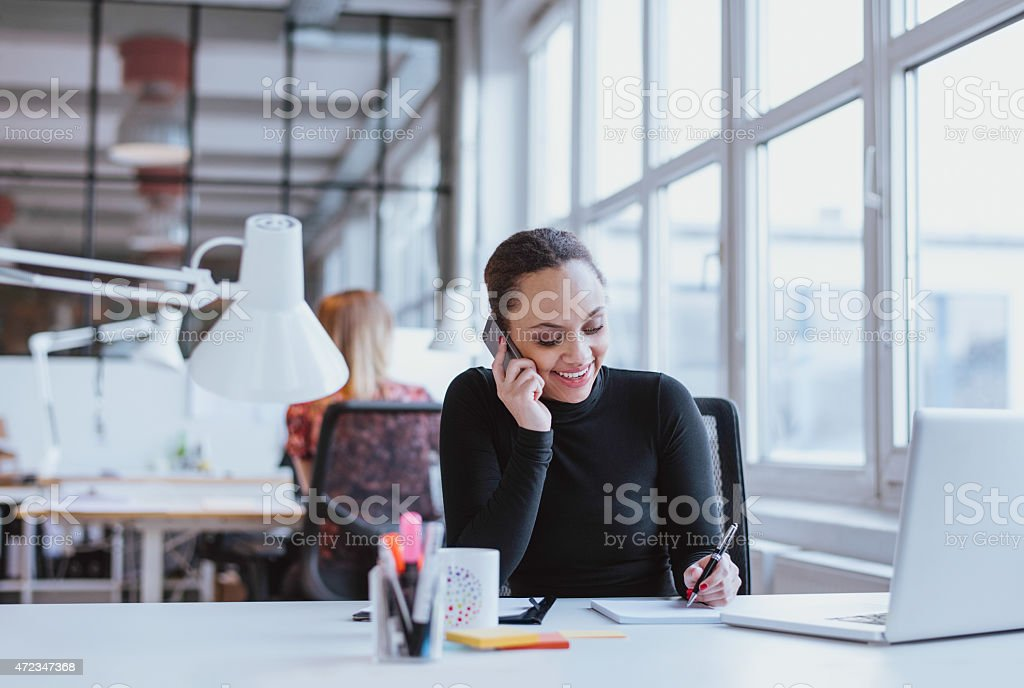 Happy young woman taking notes while talking on mobile phone stock photo