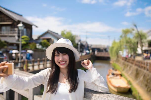 古い木の橋で写真を撮る幸せな若い女 ストックフォト