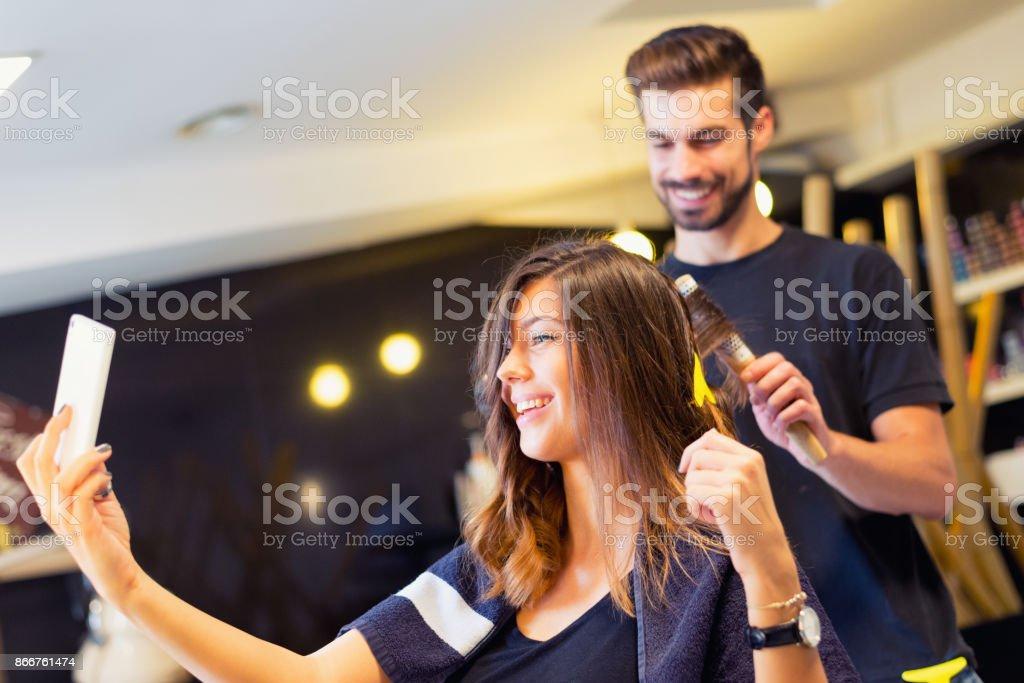 ヘアサロンで selfie を取って幸せな若い女 ストックフォト
