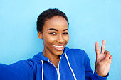 istock happy young woman taking selfie with peace hand sign 857924444