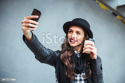 istock Happy young woman taking selfie. Woman taking selfie photo with a smarphone in the city street 947227966