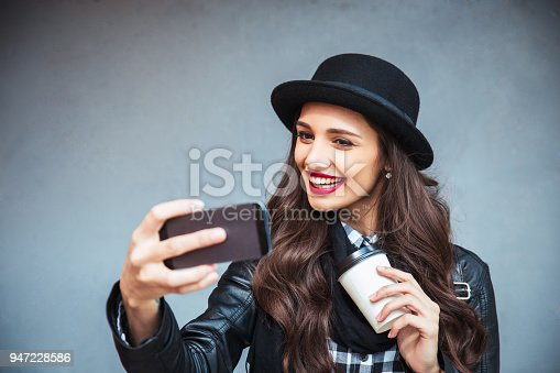 istock Happy young woman taking selfie. Woman taking selfie photo with a smarphone in the city street 947228586