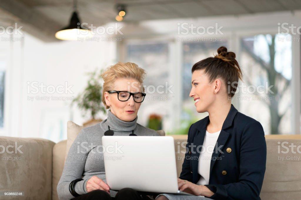 Glückliche junge Frau im Gespräch mit ihrem senior mentor Lizenzfreies stock-foto