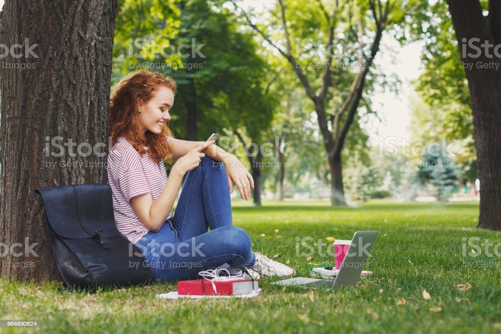 快樂的年輕婦女短信在智慧手機在公園 - 免版稅一個人圖庫照片