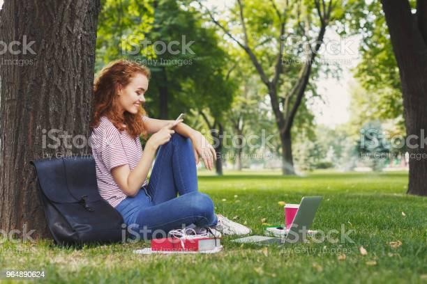 快樂的年輕婦女短信在智慧手機在公園 照片檔及更多 一個人 照片