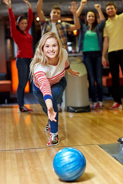 happy young woman throwing ball in bowling club stock photo
