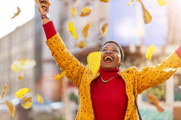 Glückliche junge Frau wirft trockene Blätter im Stadtgebiet – Foto
