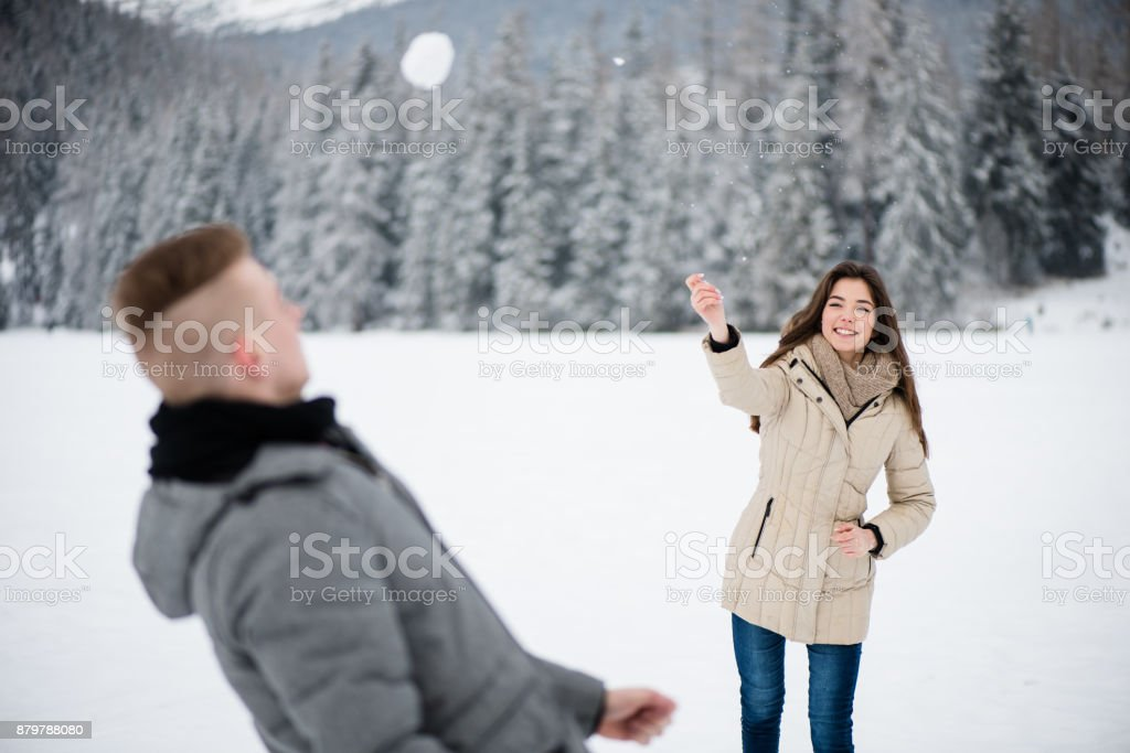 Happy young woman throwing snowball towards man stock photo