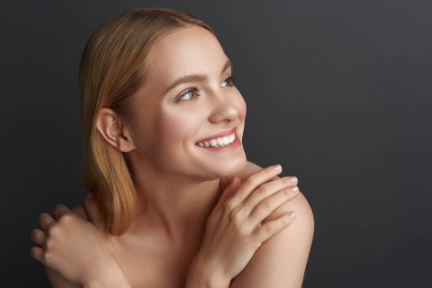 Happy young woman touching her bare shoulders and smiling stock photo