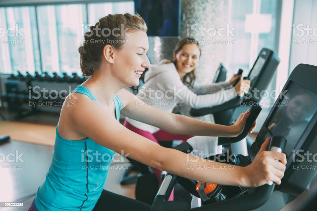 Happy Young Woman Training on Exercise Bike in Gym stock photo