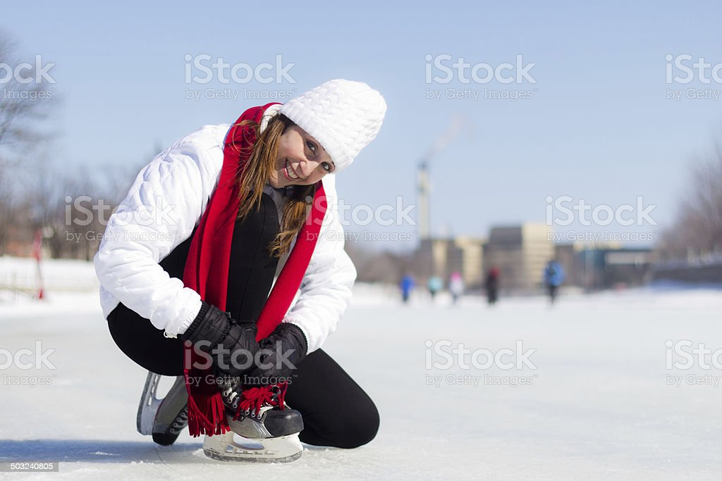Happy young woman tying her ice skates in winter stock photo