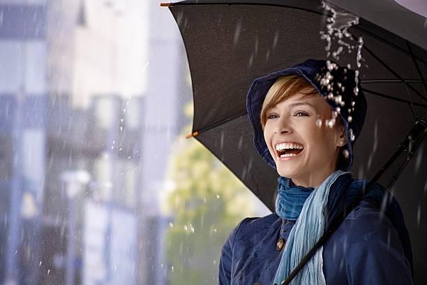 Happy young woman under umbrella in rain stock photo