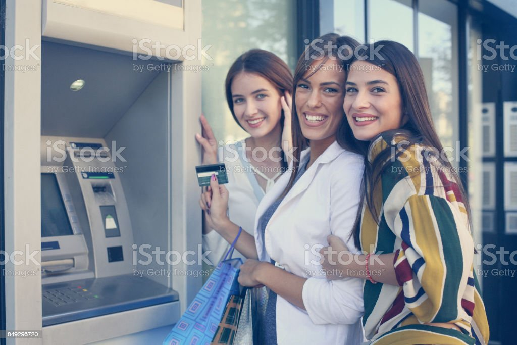 Happy young woman using cash machine. Women using credit card. Looking at camera. stock photo