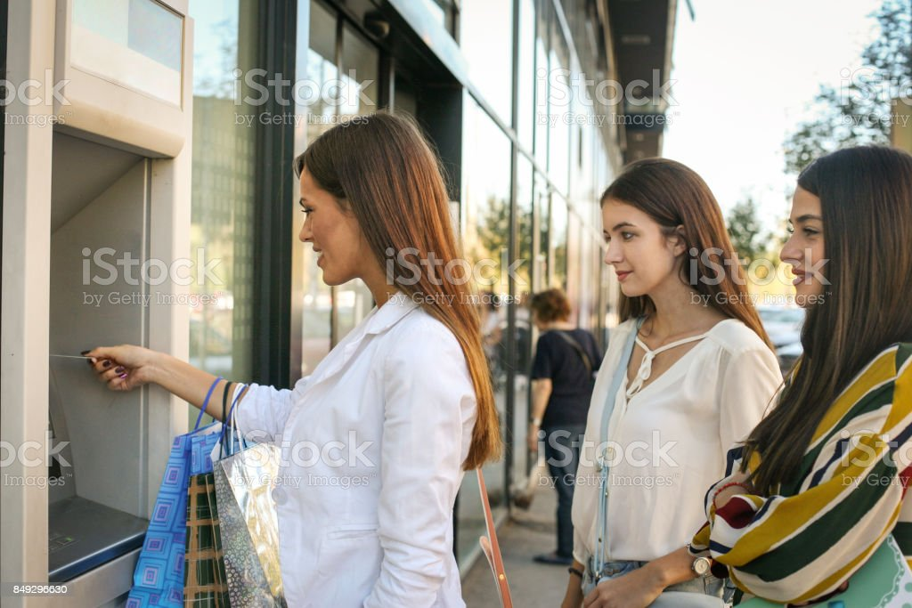 Happy young woman using cash machine. Women using credit card. stock photo