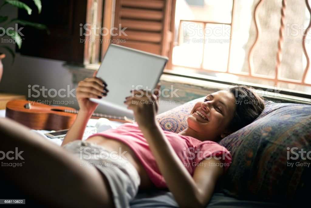 Happy young woman using digital tablet stock photo