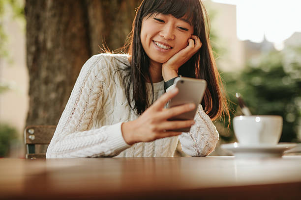 Happy young woman using her cellphone at cafe stock photo