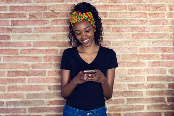 Glückliche junge Frau mit ihrem Handy, während sie vor einer Wand steht. – Foto
