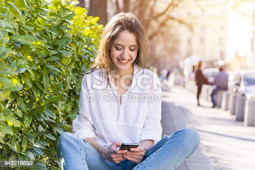 Happy young woman using phon outdoors. With copy space