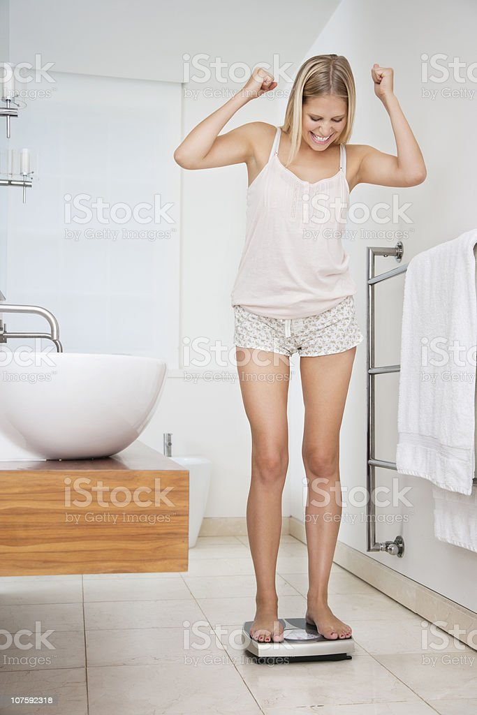 Happy young woman using scale in bathroom royalty-free stock photo