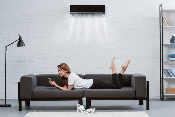 glad ung kvinna med smartphone på soffan under luftkonditioneringen hängande på väggen - kvinna ventilationssystem bildbanksfoton och bilder