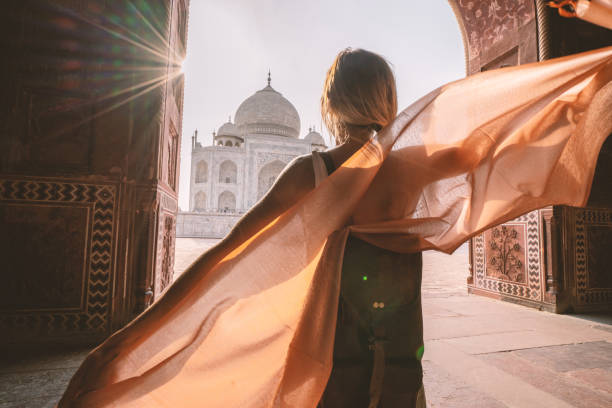 Happy young woman walking and wandering at the famous Taj Mahal at sunrise holding scarf in hands, Agra, India. People travel Asia concept stock photo