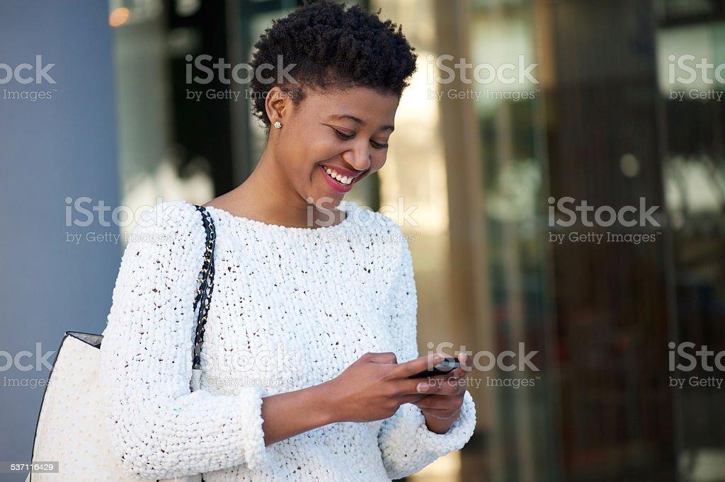 d57f1947e Mulher jovem feliz andando na cidade o envio de mensagem de texto foto  royalty-free