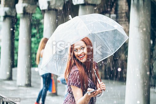 Young redheaded woman with purple top holding an umbrella and a phone, walking under the rain. Columns and a woman with purchases on background.