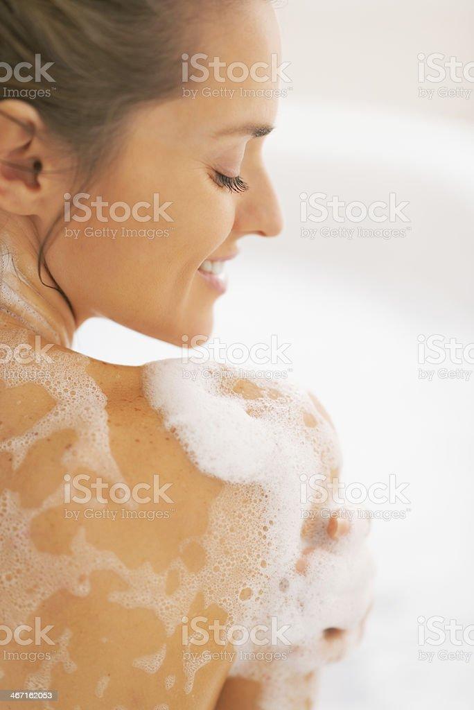 happy young woman washing in bathtub stock photo