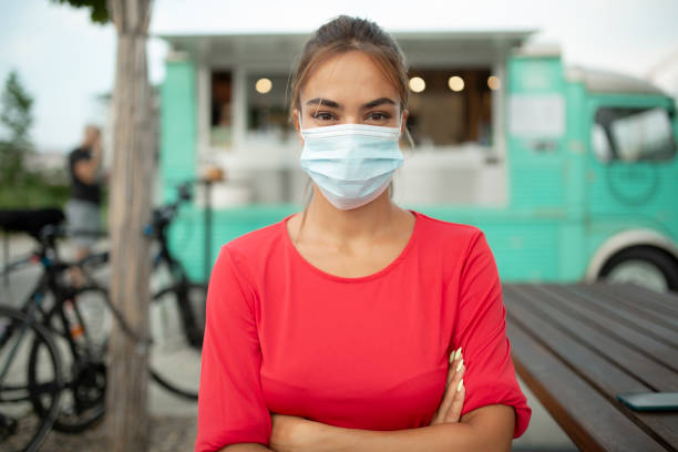 Happy young woman wearing a face mask stock photo