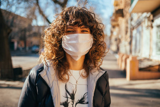 Happy young woman wearing facial mask for virus protection stock photo