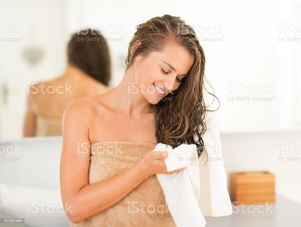 happy young woman wiping hair with towel in bathroom stock photo
