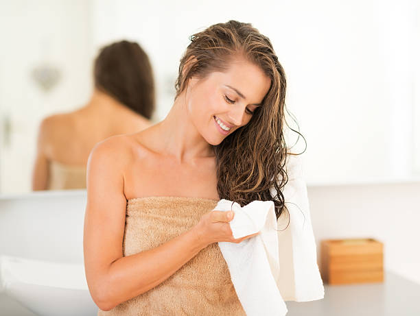 happy young woman wiping hair with towel in bathroom - human hair stock photos and pictures