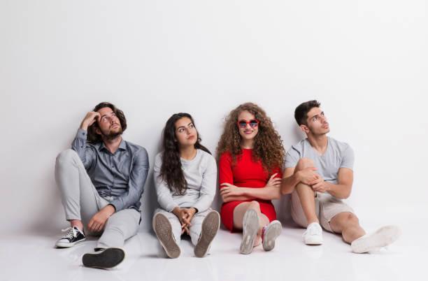 Eine glückliche junge Frau mit einer Gruppe befreundeter gelangweilt sitzen auf dem Boden. – Foto