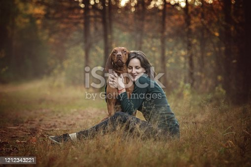 Happy young woman having fun with a hungarian viszla dog during a walk in the autumn forest