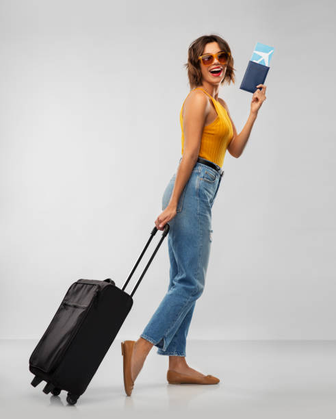 happy young woman with air ticket and travel bag stock photo