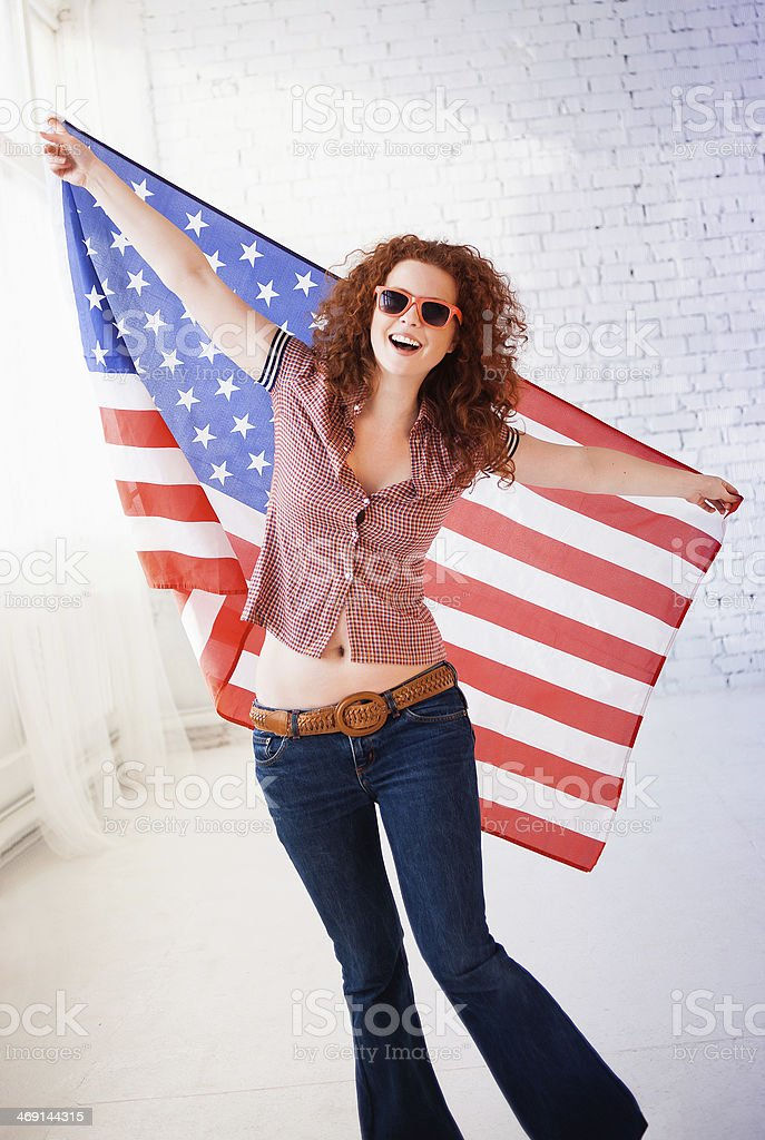 Happy young woman with American flag stock photo