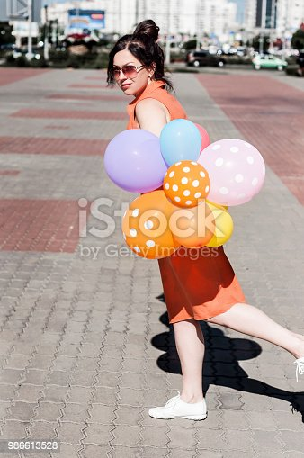 624206636 istock photo happy young woman with balloons on the city square 986613528