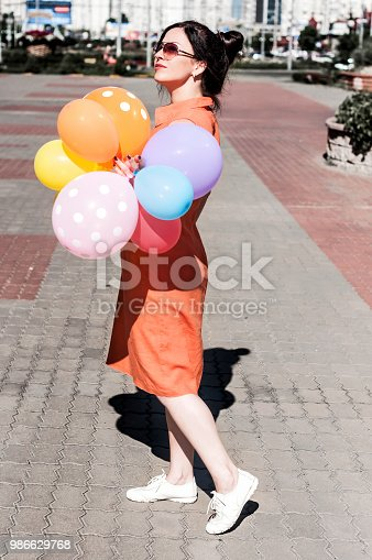 624206636 istock photo happy young woman with balloons on the city square 986629768