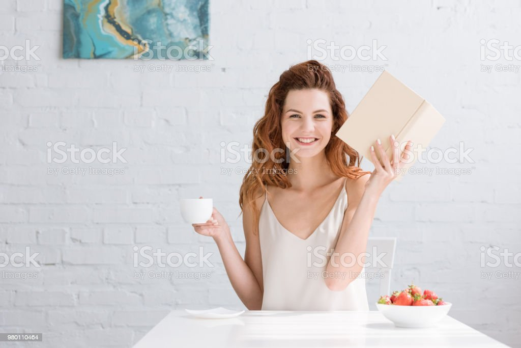 happy young woman with book and cup of coffee looking at camera at home stock photo