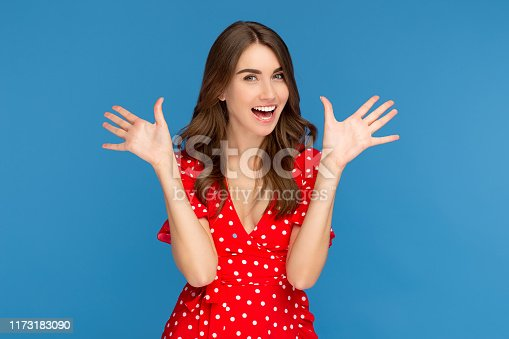 Happy young woman with bright smile in red casual dress looking up with excited face waving hands over blue background