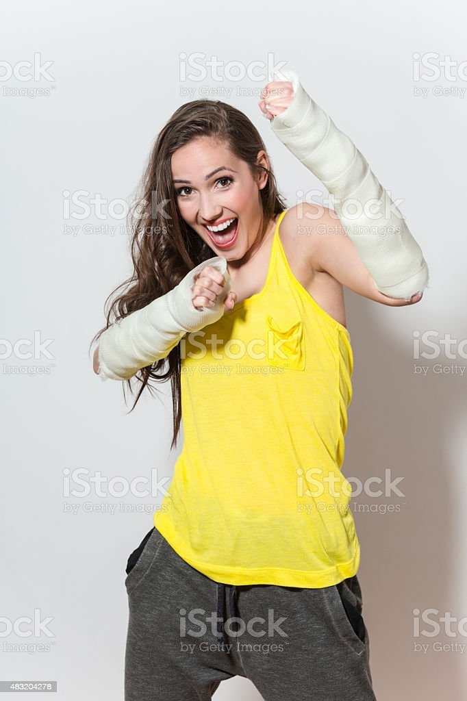 Happy young woman with broken arms stock photo