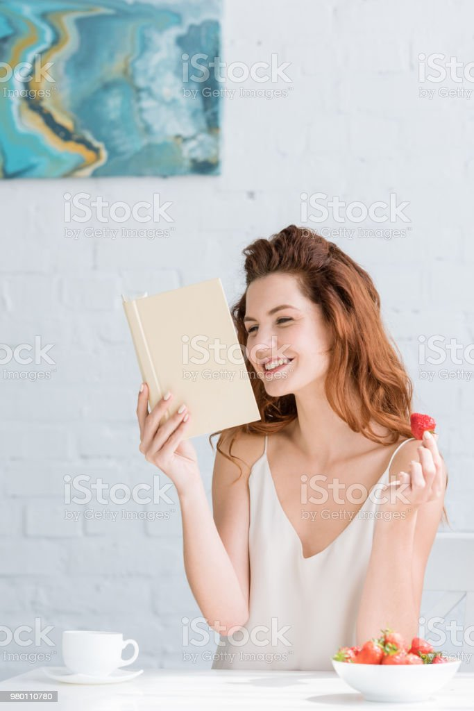 happy young woman with coffee and strawberry reading book at home stock photo