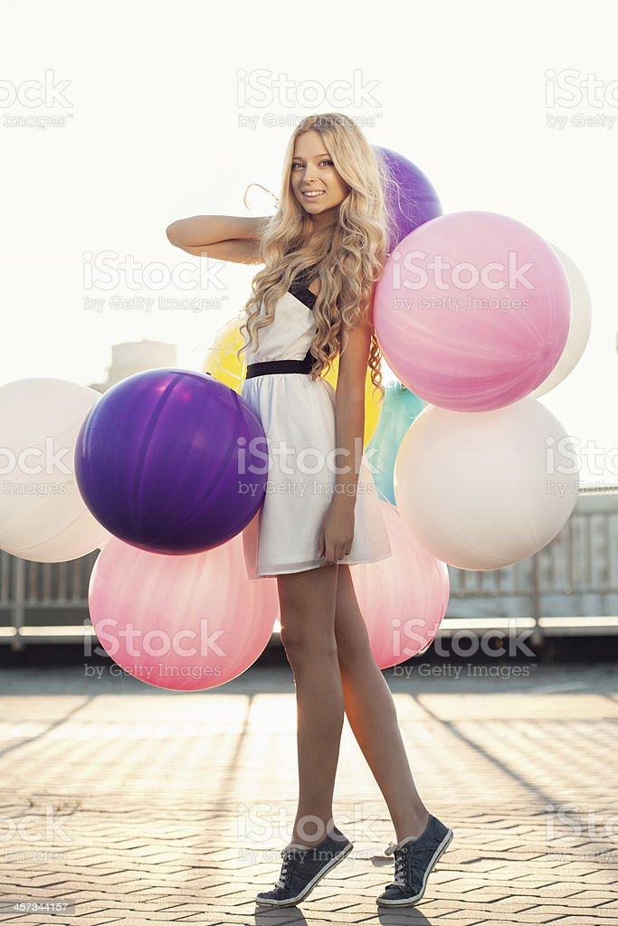 Happy young woman with colorful latex balloons stock photo